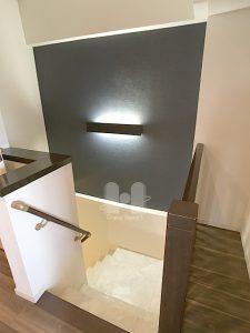 階段上部壁面はダークなアクセントクロスに間接照明を設置したおしゃれな仕上がりです。