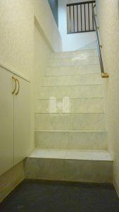 玄関から、白大理石調シートを貼り込んだ階段を昇って室内へ。